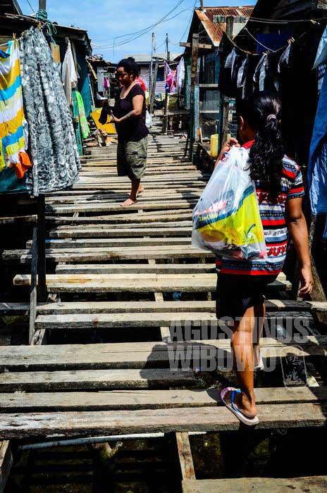 Awas tercebur melintasi jalan kayu perkampungan atas air Hanuabada. (AGUSTINUS WIBOWO)