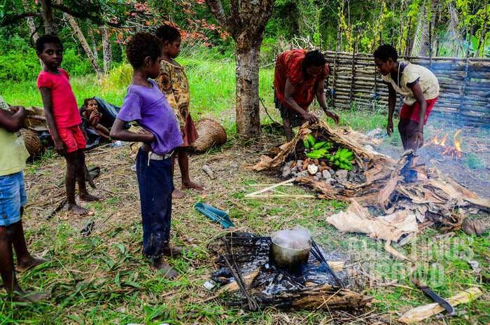 Mereka memasak dengan cara tradisional: membakar pisang dan ketela di atas batu panas (AGUSTINUS WIBOWO)