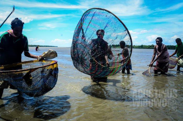 Para perempuan menangkap ikan dengan jaring