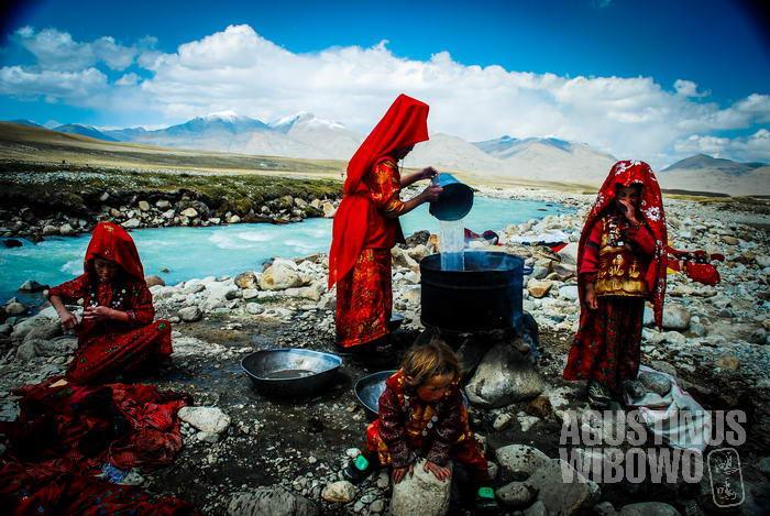 Para perempuan merebus air untuk mencuci baju
