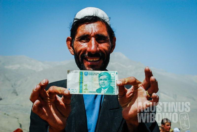 Pedagang Afghan menunjukkan mata uang Somoni yang digunakan di pasar bersama antara kedua negara.