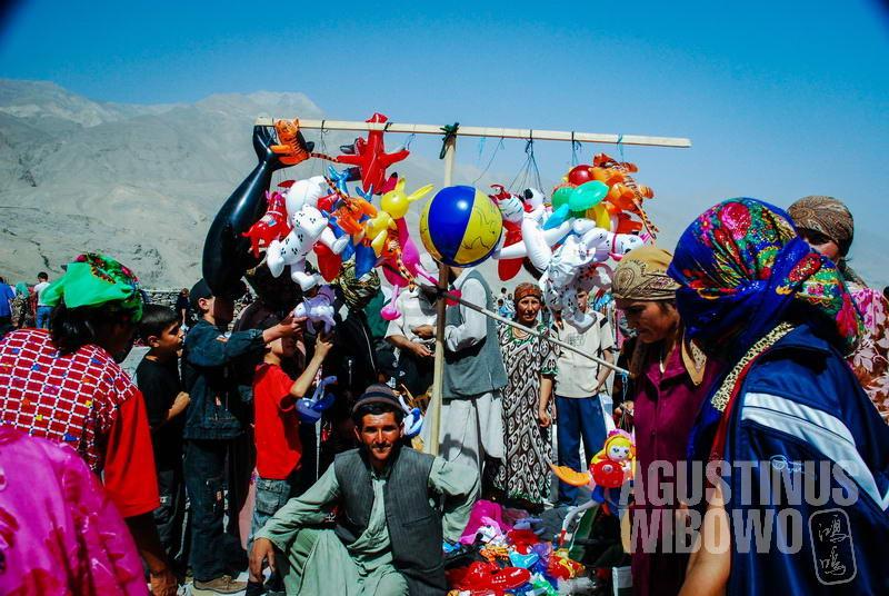 Para perempuan Tajik berbelanja barang yang ditawarkan pedagang Afghan di pasar internasional di Ishkashim.