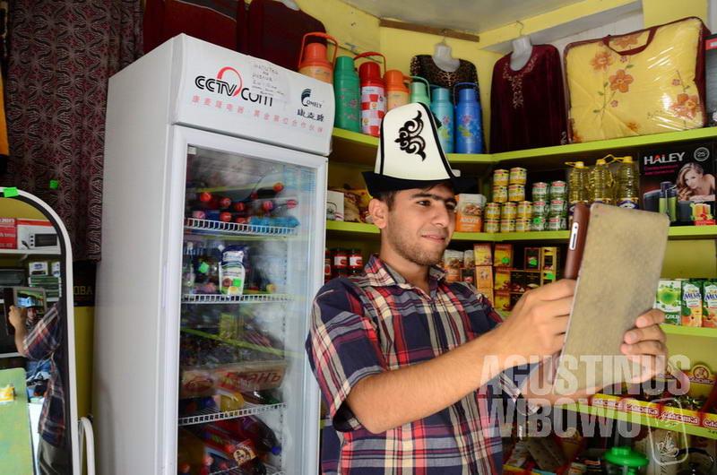 Seorang pemuda Tajik mencoba topi kalpak khas bangsa Kirgiz.