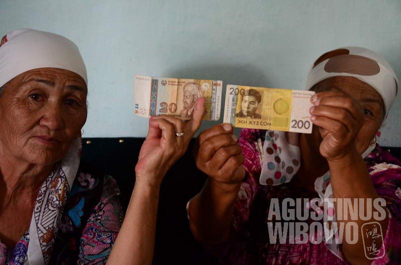 Para perempuan Kirgiz menunjukkan bahwa di sini berlaku dua mata uang sekaligus.