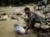 Penduduk lokal berusaha menambang emas yang mengalir di sungai dengan cara tradisional