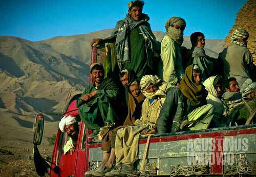 Villagers travelling on the truck in Afghanistan western provinces. The central route of Afghanistan connecting Herat to Kabul is unpaved for about 900 km. Public transport is extremely difficult and villagers rely on hitchhiking trucks to travel around.