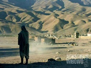 A man looking at the rugged mountains beyond the village of Chihst o Sharif.