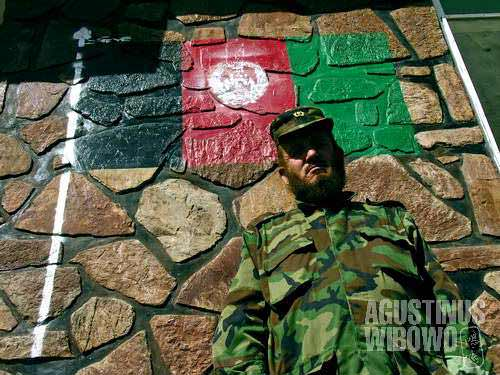 An Afghan military commander under the tricolor flag of Afghanistan painted on wall of soldier dormitory in Chekhcheran.