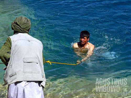 A Shiite pilgrim is dipping into the cold water of Band-e-Haibat, the holiest among 6 lakes of Band-e-Amir. The Shiites believe that the miraculous Band-e-Amir were created by their Imam, Hazrat Ali, and dipping into the water is believed to heal all sicknesses.