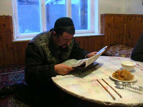 Reading Dungan newspaper before dinner