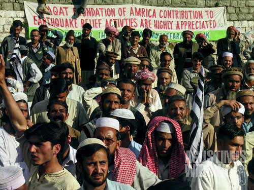"""Protesters yelling """"Death to America"""", in front of a banner stating that help from an American fondation is highly appreciated"""