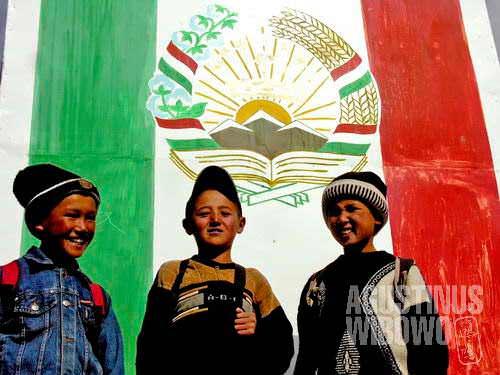 Boys of Murghab, in front of Tajik banner with the tricolor flag and coat-of-arms, of which important element is a snow mountain