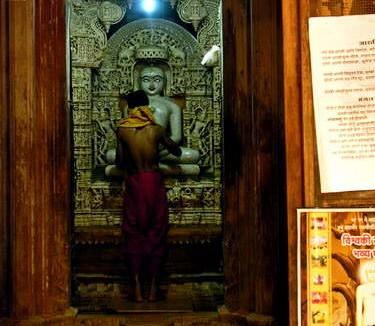 'Orang suci' menyiapkan sesaji di hadapan patung thirtankar agama Jain (AGUSTINUS WIBOWO)
