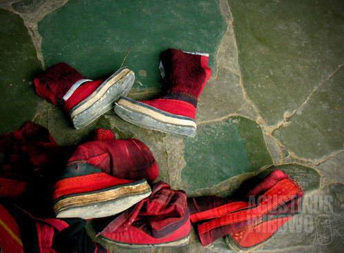 Sepatu biksu berserakan di depan ruang pembacaan sutra (AGUSTINUS WIBOWO)